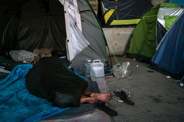 A migrant sleeps outside a tent in the port of Piraeus, where nearly 1,500 refugees and migrants live in a make-shift camp in Athens on July 17, 2016. In partnership with local aid groups Faros and...