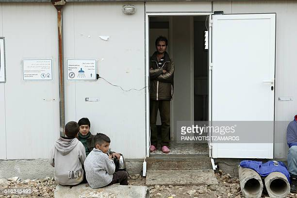 A migrant stands at the shower cabin at the refugee camp in Schisto western suburb of Athens on March 18 2016 / AFP PHOTO / Panayotis TZAMAROS