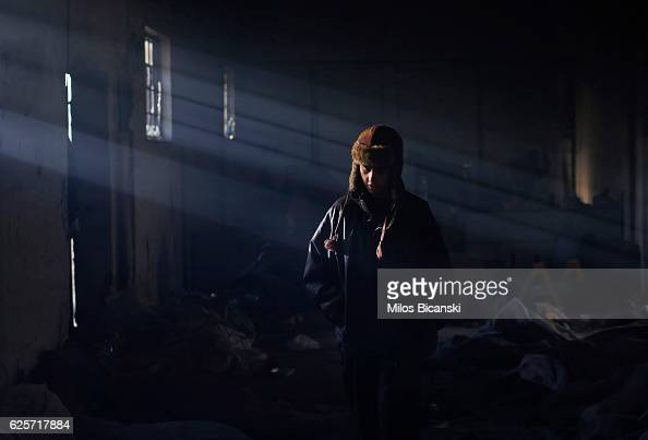 A migrant stands in an abandoned warehouse on November 25 2016 in Belgrade Serbia About 1000 migrants are living without any basic living conditions...