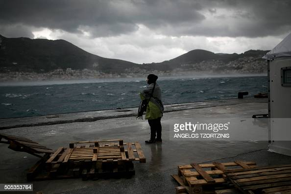 A migrant stands in front of a tent of the UNHCR at the registration center on the Greek island of Samos on January 17 2016 / AFP / ANGELOS TZORTZINIS