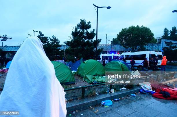A migrant stands near tents as French antiriot police force CRS officers prepare the evacuation of a makeshift camp at Porte de la Chapelle in the...