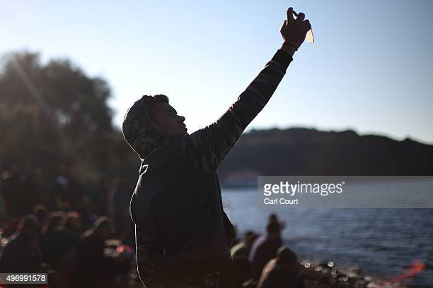 A migrant takes a selfie photograph after making the crossing from Turkey to the Greek island of Lesbos on November 13 2015 in Sikaminias Greece...