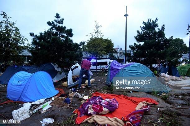 A migrant takes down his tent as French police ready to evacuate him and others from a makeshift camp at Porte de la Chapelle in the north of Paris...