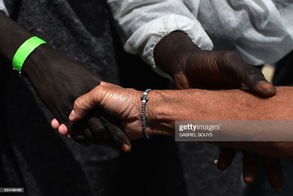 A migrant thanks a doctor of French NGO Doctors Without Borders (MSF) aboard rescue ship 'Aquarius' as they arrive in the port of Cagliari, Sardinia, on May 26, 2016, two days after being rescued near the Libyan coasts. The Aquarius is a former North Atlantic fisheries protection ship now used by humanitarians SOS Mediterranee and Medecins Sans Frontieres (Doctors without Borders) which patrols to rescue migrants and refugees trying to reach Europe crossing the Mediterranean sea aboard rubber boats or old fishing boat. / AFP / GABRIEL