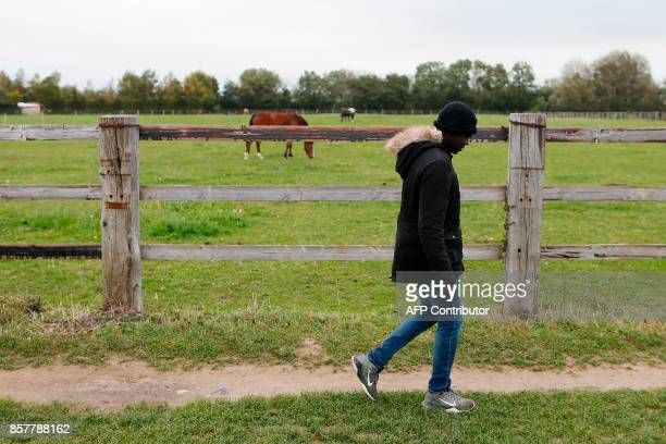 A migrant walks from a forest to the port in Ouistreham near Caen northwestern France on October 5 2017 Migration is a hot button issue in Europe and...