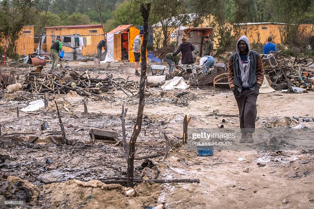 A migrant walks in the middle of burnt tents after a massive brawl that left 40 people injured in the 'Jungle' migrant camp in the northern French town of Calais on May 27, 2016. Some 20 people living in the 'Jungle' refugee camp in the northern French port of Calais were injured in a brawl between around 200 Afghans and Sudanese on May 26, 2016. / AFP / PHILIPPE