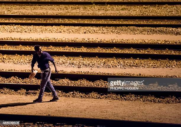 A migrant walks on rail tracks in the Channel Tunnel site in Frethun northern France on August 5 2015 The European Commission offered August 4 to...
