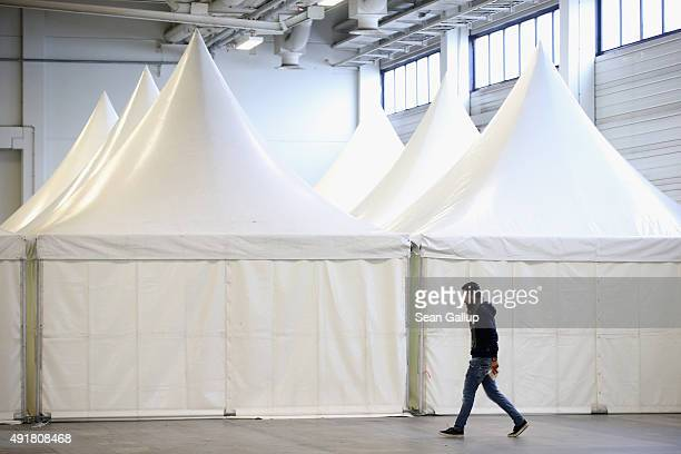 A migrant walks past tents for families at a temporary shelter for migrants opened this week in a hall of the Berliner Messe trade fair grounds on...