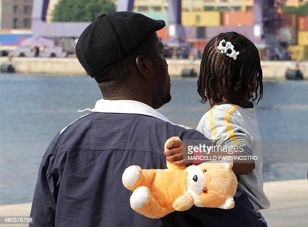 CROP** A migrant walks with an orphaned child from Sierra Leone after disembarking from the Italian Coast Guard patrol vessel Dattilo on July 11 at...