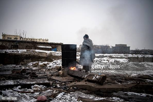 TOPSHOT A migrant warms up next to a fire outside a derelict warehouse used as a shelter near Belgrade's main railway station on January 17 with...