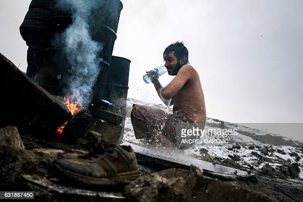 TOPSHOT A migrant washes himself outside a derelict warehouse used as a shelter near Belgrade's main railway station on January 17 with temperatures...