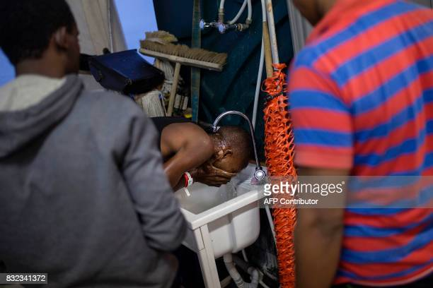 A migrant washes his face on the deck of the Aquarius rescue ship run by NGO SOS Mediterranee and Medecins Sans Frontieres after his transfer from...