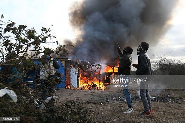 A migrant watches a hut burn as police officers clear part of the 'jungle' migrant camp on February 29 2016 in Calais France The French authorities...
