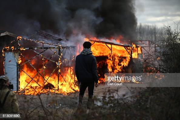A migrant watches as a hut burns as police officers clear part of the 'jungle' migrant camp on February 29 2016 in Calais France The French...