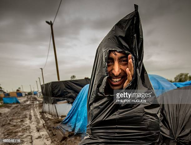A migrant who protects himself from the rain with a plastic trash bag walks through a mudpath of the 'New Jungle' migrant camp in Calais where...