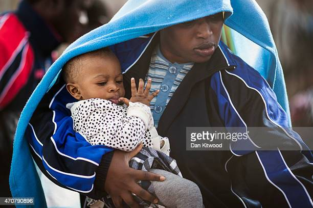 A migrant woman and a young child board a ship bound for Sicily on April 23 2015 in Lampedusa Italy It is expected that EU leaders in Brussels are to...