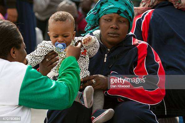 A migrant woman and a young child wait to board a ship bound for Sicily on April 23 2015 in Lampedusa Italy It is expected that EU leaders in...
