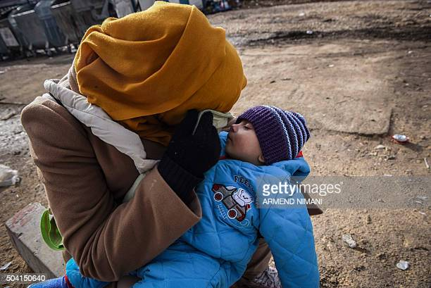A migrant woman and her todler wait for a bus at a transit camp in southern Serbian town of Presevo on January 9 2016 More than a million refugees...