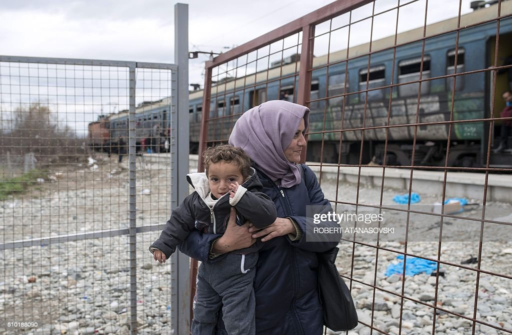 A migrant woman carries a child as she waits to board a train after crossing the Greek-Macedonian border, near Gevgelija, on February 14, 2016. Dutch Foreign minister Bert Koenders on February 14 spent an hour in a Vinojug recipient center near Gevgelija talking with migrants, children, UNICEF and Red Cross representatives, police and others members that are taking care of migrants that are heading to the EU from devastated homes in Syria, Afghanistan and Iraq. / AFP / Robert ATANASOVSKI