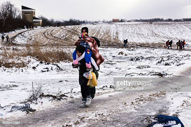 A migrant woman carries her child as she walks across a snowcovered after crossing the Macedonian border into Serbia near the village of Miratovac on...