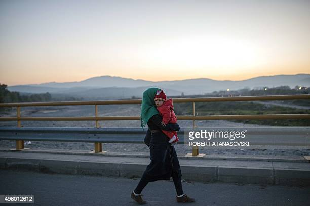 A migrant woman carrying her child walks to catch a bus heading to Serbia on November 6 after leaving a registration centre near Gevgelija The flow...