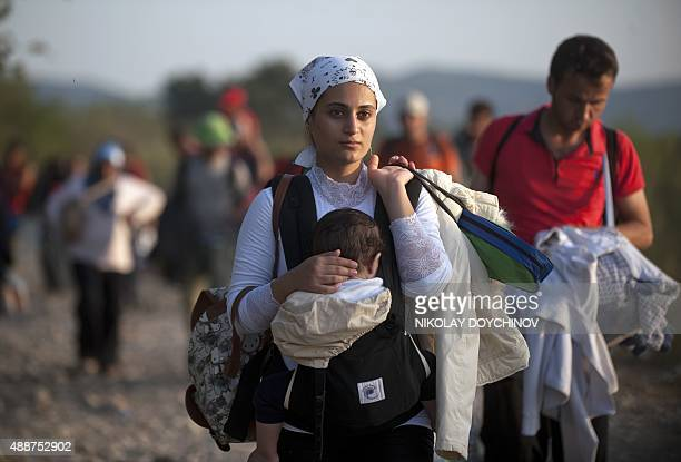 A migrant woman carrying her sleeping child crosses the GreekMacedonian border near the town of Gevgelija on September 17 2015The European Parliament...