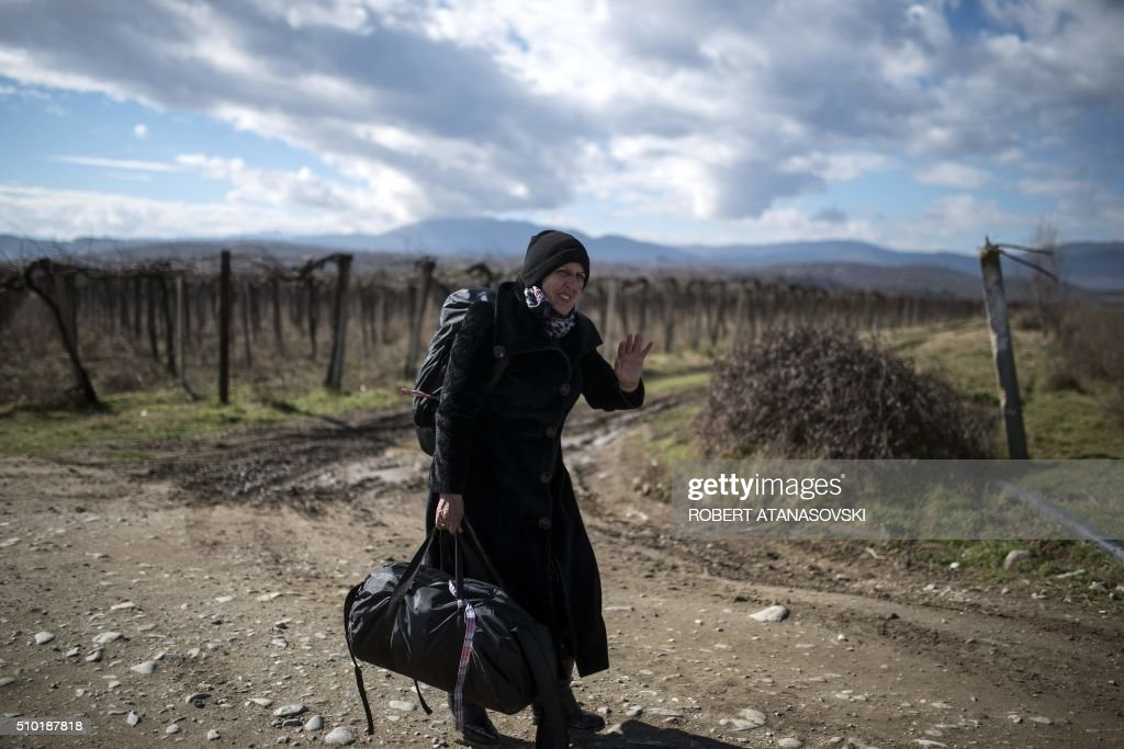 A migrant woman crosses the Greek-Macedonian border near the town of Gevgelija, on February 14, 2016. Dutch Foreign minister Bert Koenders on February 14 spent an hour in a Vinojug recipient center near Gevgelija talking with migrants, children, UNICEF and Red Cross representatives, police and others members that are taking care of migrants that are heading to the EU from devastated homes in Syria, Afghanistan and Iraq. / AFP / Robert ATANASOVSKI