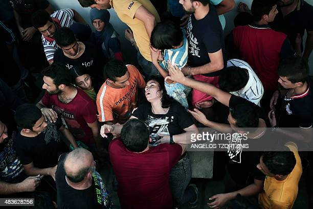 A migrant woman faints within a registration procedure at the stadium on the Greek island of Kos on August 11 2015 Police on the Greek island on Kos...