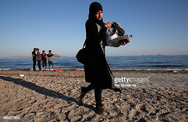 A migrant woman from Syria leaves the beach after completing a journey with fellow travelers in a small dinghy crossing a three mile stretch of the...