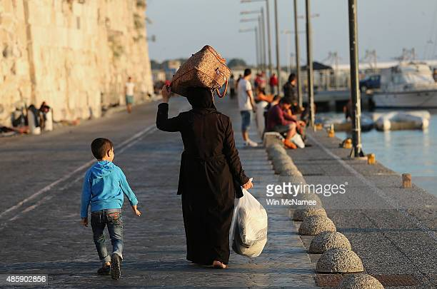 A migrant woman from Syria with her son following behinf her carries her suitcase on her head as she walks to the port for transit to Athens on...