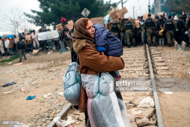 A migrant woman holding a baby crosses a railway track in front of Macedonian policemen and migrants demonstrating after she crossed GreekMacedonian...