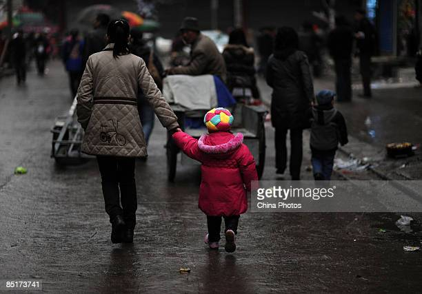 A migrant woman leading her child walks at a street on March 1 2009 in Wuhan of Hubei Province China China is facing a difficult employment situation...