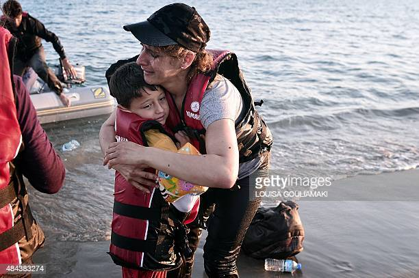 A migrant woman reacts while hugging her son after safely arriving to the shores of the Greek island of Kos on August 18 2015 Authorities on the...
