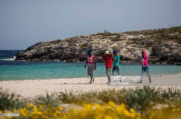 Migrant women walk across a beach on April 23 2015 in Lampedusa Italy It is expected that EU leaders in Brussels are to agree later that only 5000...