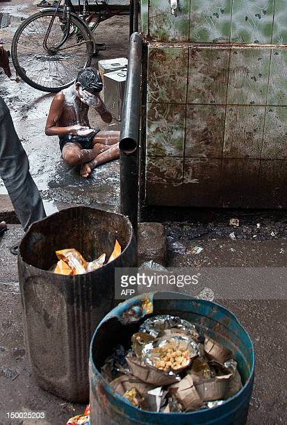 A migrant worker bathes at a roadside tap in New Delhi on August 9 2012 Thousands of migrant workers are engaged in various projects in the national...