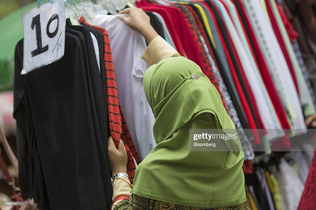 A migrant worker browses clothes in Victoria Park in Hong Kong, China, on Sunday, Nov. 11, 2012. Hong Kong's more than 300,000 domestic workers cook, clean and take care of children and the elderly. Photographer: Jerome Favre/Bloomberg via Getty Images