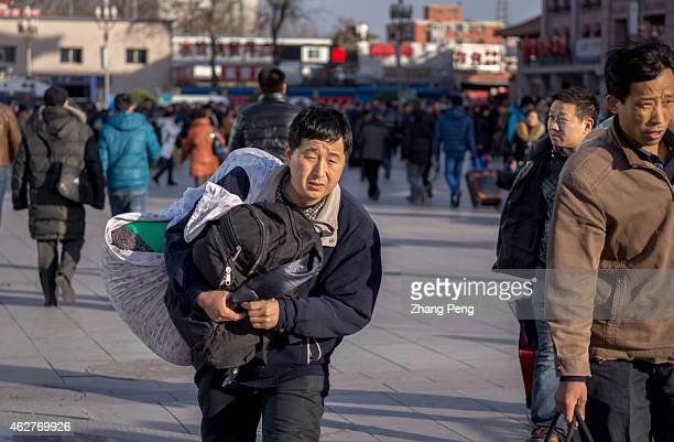 A migrant worker carries his luggage hurrying to Beijing railway station China's 40day spring travel rush called 'chunyunthe largest annual migration...