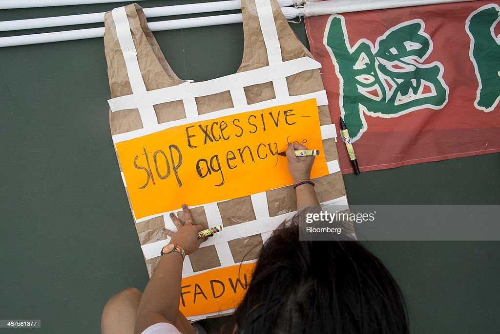 A migrant worker makes a sign advocating against excessive agency fees during a labor day rally in Hong Kong, China, on Thursday, May 1, 2014. Thousands of people have marked labor day by staging a series of rallies to demand better workers' rights. Photographer: Brent Lewin/Bloomberg via Getty Images