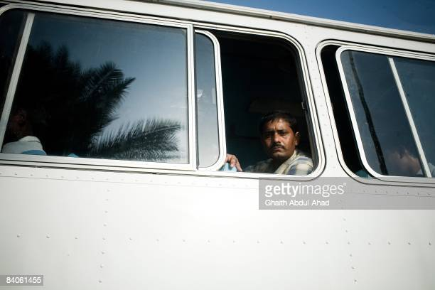 A migrant worker sits in a bus returning him to the labor camps located outside the city after a day of work July 18 2008 in Dubai United Arab...