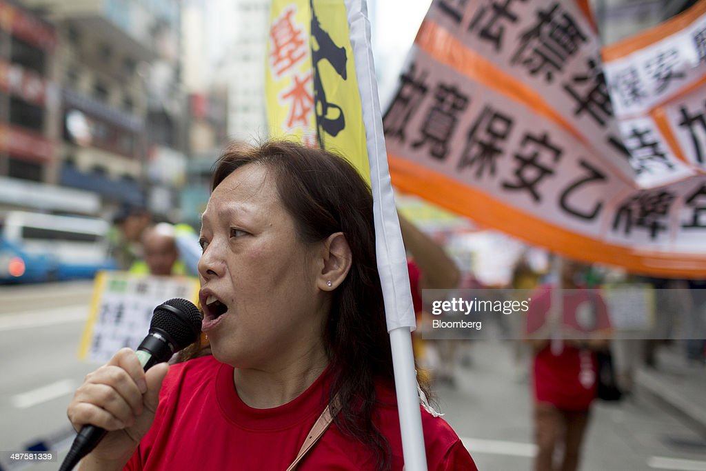 A migrant worker speaks into a microphone during a labor day rally in Hong Kong, China, on Thursday, May 1, 2014. Thousands of people have marked labor day by staging a series of rallies to demand better workers' rights. Photographer: Brent Lewin/Bloomberg via Getty Images