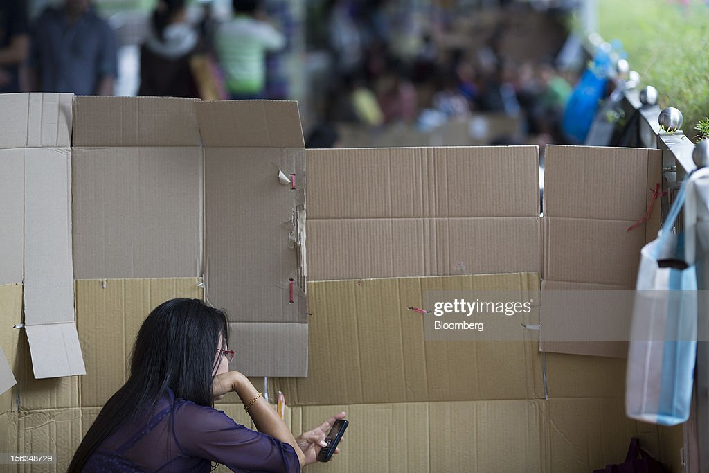 A migrant worker uses her mobile phone on her day off in the Central district of Hong Kong, China, on Sunday, Nov. 11, 2012. Hong Kong's more than 300,000 domestic workers cook, clean and take care of children and the elderly. Photographer: Jerome Favre/Bloomberg via Getty Images