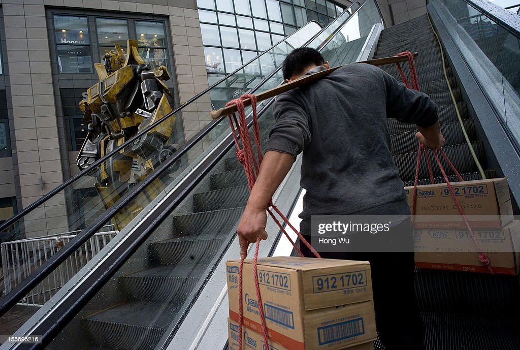 A migrant worker uses his shoulder pole to carry goods on an escalator passing by a transformer statue at a shopping mall on November 6, 2012 in Chongqing, China.