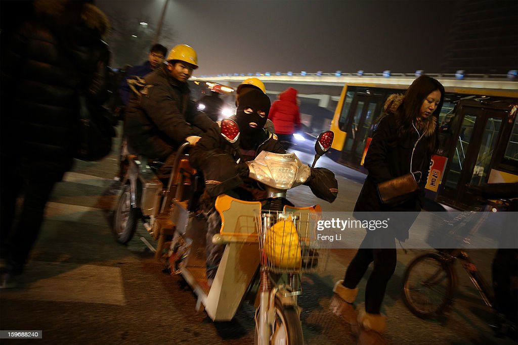 A migrant worker wearing a headgear rides the tricycle passing the central business district during severe pollution on January 18, 2013 in Beijing, China.