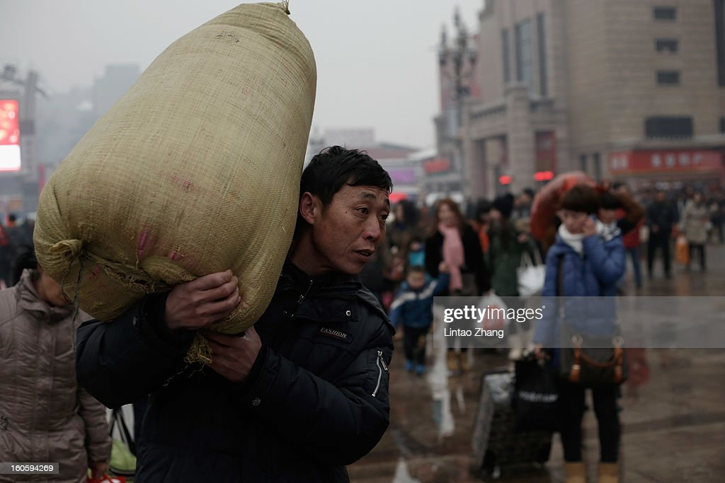 Migrant workers arrive at the Beijing Railway Station with their luggage on February 3, 2013 in Beijing, China. The Spring Festival travel season runs from January 26 to March 6 and according to reports road passenger transport in China is estimated at 3.1 billion people during this time of year.