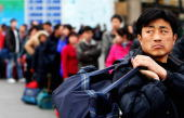 Migrant workers arrive at the West Railway Station with their luggage on February 2 2009 in Beijing China After Chinese New Year holiday thousands of...