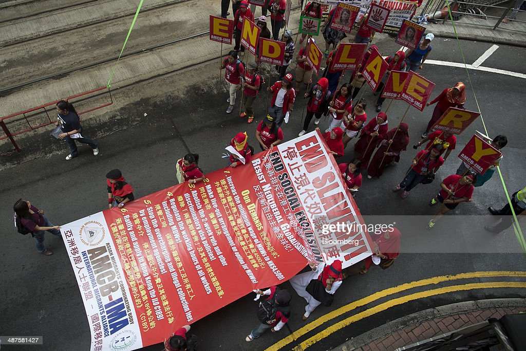 Migrant workers carry a banner displaying 'end slavery' as they walk on a street during a labor day rally in Hong Kong, China, on Thursday, May 1, 2014. Thousands of people have marked labor day by staging a series of rallies to demand better workers' rights. Photographer: Brent Lewin/Bloomberg via Getty Images