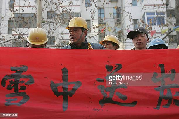 Migrant workers in an action to ask for default wages display a banner with a Chinese idiom featuring 'It's much appreciated if you send charcoal...