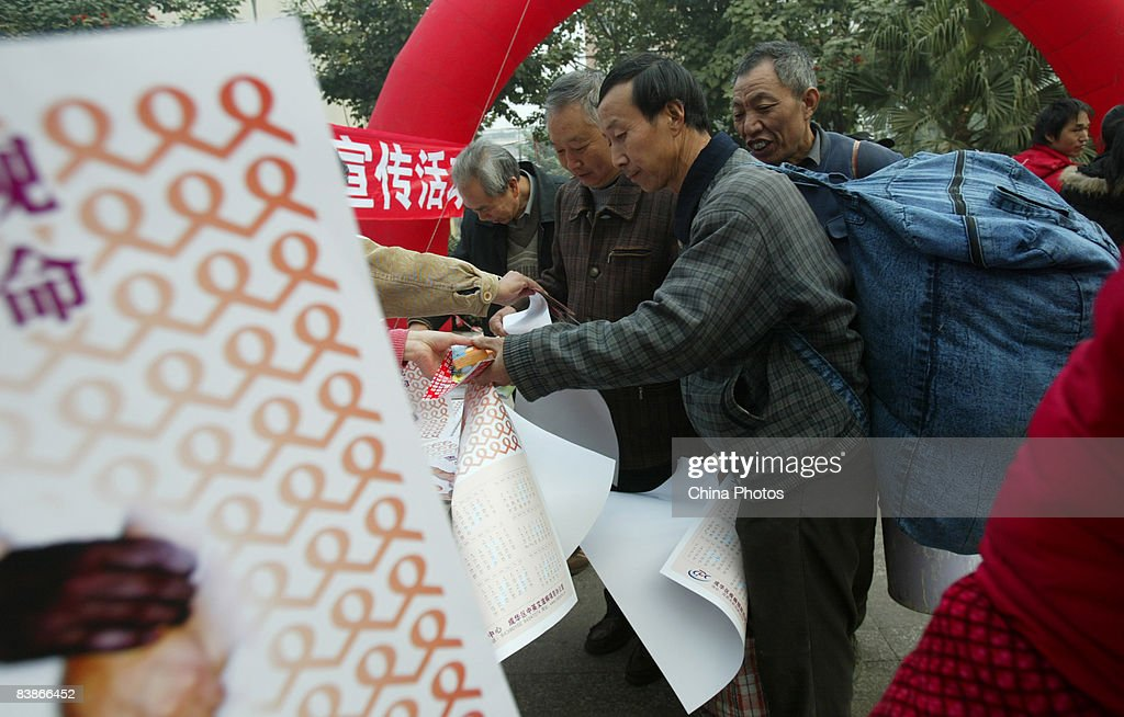 Migrant workers line up to get calendars, leaflets and condoms during an AIDS awareness promotion held to mark the World AIDS Day on December 1, 2008 in Chengdu of Sichuan Province, China. According to official estimates, China has 700,000 people living with HIV with an estimated 85,000 with AIDS.
