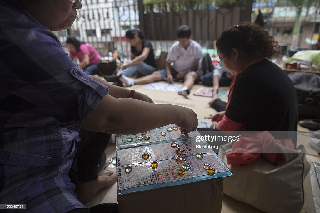 Migrant workers play bingo on their day off in the Central district of Hong Kong, China, on Sunday, Nov. 11, 2012. Hong Kong's more than 300,000 domestic workers cook, clean and take care of children and the elderly. Photographer: Jerome Favre/Bloomberg via Getty Images