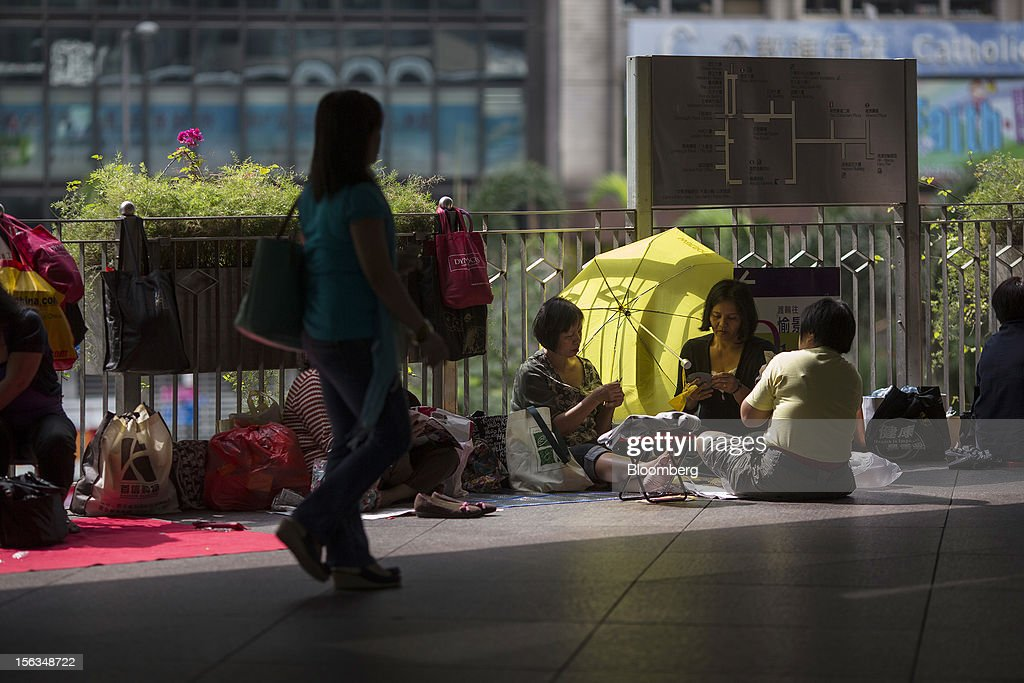 Migrant workers play cards on their day off in Central district in Hong Kong, China, on Sunday, Nov. 11, 2012. Hong Kong's more than 300,000 domestic workers cook, clean and take care of children and the elderly. Photographer: Jerome Favre/Bloomberg via Getty Images